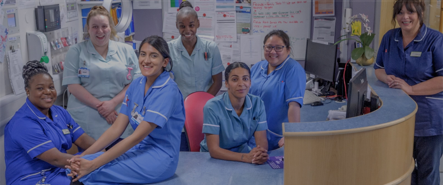 Smiling nurses assembled around ward reception desk